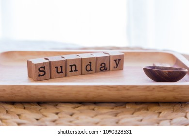 Letters wording SUNDAY wooden cubes on tray in bedroom with tea spoon, soft white curtain on background, daylight from window. Concepts of happy day or weekend for relax.