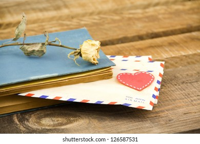 letters and yellow rose in a book