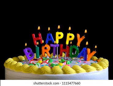 Letter Shaped Candles Spell Happy Birthday On Top Of A Cake