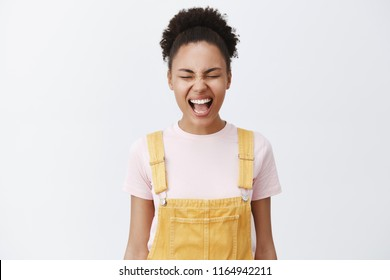 Letting emotions out feels good. Careless beautiful African American with smooth and clean skin in yellow overalls, shouting with closed eyes, releasing stress, trying calm down over grey wall