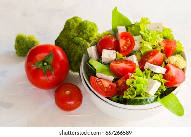Lettuce leaves, cherry tomatoes, cucumber, broccoli and tofu salad on white background.