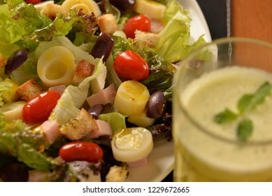 lettuce salad, cherry tomatoes, heart of palm, fresh cheese, black olives and cooked ham and pineapple juice with mint