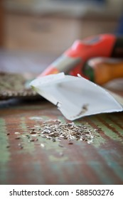 Lettuce seeds and a packet on a table with a soiled trowel in the background