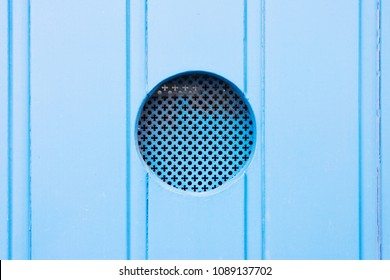 Leuca, Apulia, Italy - A traditional old metal peephole in a blue wooden door