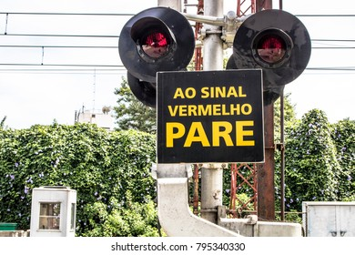 """Level crossing between the street and railroad with traffic light and write """"to the red stop sign"""" in Portuguese, in Sao Paulo"""