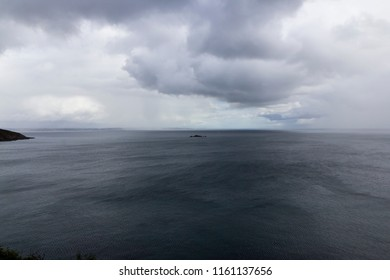 Level horizon view of sea with rain and grey clouds