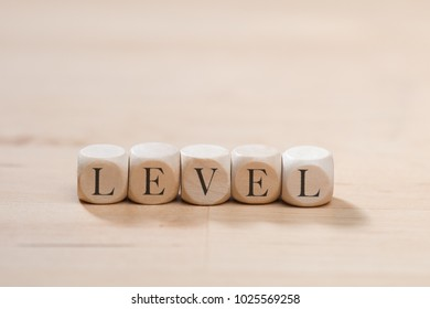 Level word on wooden cubes. Level concept