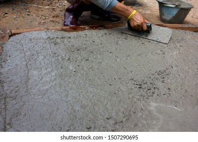 leveling and screeding concrete floor base with square trowel in front of the house