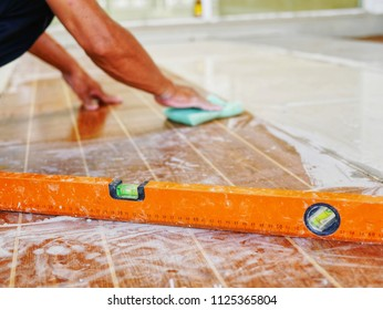 Leveling tools on dirty floor tiles with blurry working hands cleaning tile surface