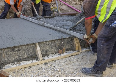 Leveling wet concrete with a metal screed. Worker hands using a screed board to level the surface. Selective focus and shallow dof.
