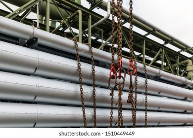 Leverkusen, Germany - September 12, 2019: Chains and hooks of a crane, ready to lift the tubes of an insulated heat exchanger from a special truck