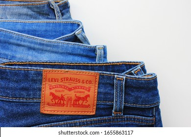 Levi's blue jeans pile isolated on white background in Moscow on February 2020. Blue denim Levi Strauss jeans, top view of classic Levis pants with leather brand label