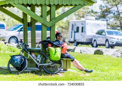 Levis, Canada - June 4, 2017: Male person, man with bicycle at rest area stop by highway in Quebec province on scenic road trip taking break, relaxing