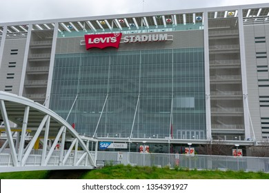 Levi's Stadium home of the San Francisco 49ers of the National Football League with white steel pedestrian bridge spanning San Tomas Creek - Santa Clara, California, USA - March 27, 2019