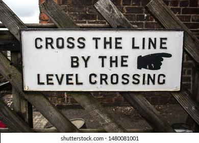 Levisham / Great Britain - July 14, 2019 : Heritage restored railway station sign advising passengers to cross the railway line via the level crossing at  Levisham station sign displayed.