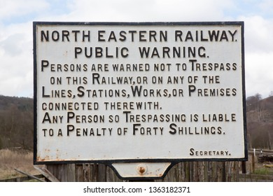 LEVISHAM STATION, NORTH YORKSHIRE, ENGLAND, APRIL 4 2019 Old historic North Eastern Railway sign with the warning of not to trespass on the railway.