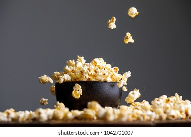 Levitating falling popcorn in a ceramic bowl and around it. Side view.