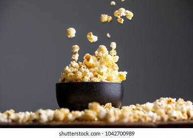 Levitating falling popcorn in a ceramic cup and around it. Side view.