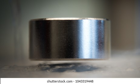 levitating neodymium magnet. A levitating magnet over a superconductor filled with liquid nitrogen