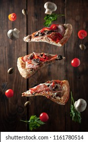 Levitating pizza and vegetables. Three pieces of pizza, tomatoes, olives, parsley, champignons.