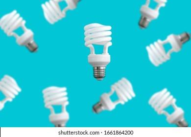 levitating spiral energy saving light bulbs on blue background, energy saving and eco friendly life  concept