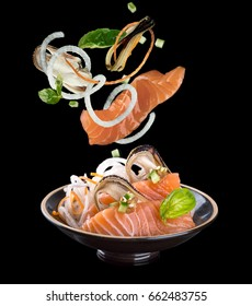Levitation sashimi with salmon and mussel in a black plate. On a black background with reflection.