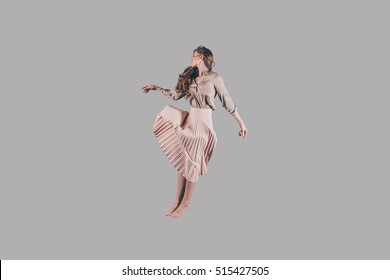 Levitation. Studio shot of attractive young woman in beautiful dress hovering in air