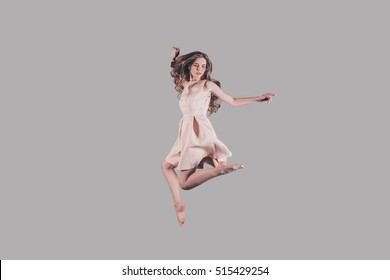 Levitation. Studio shot of attractive young woman hovering in air