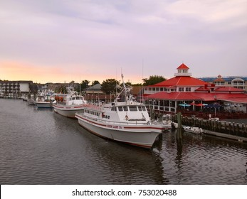 LEWES, DELAWARE - AUGUST 29, 2017: Tour boats and fishing boats are moored in the harbor at sunset in Lewes, Delaware, a United States eastern shore town rich in Civil War history.