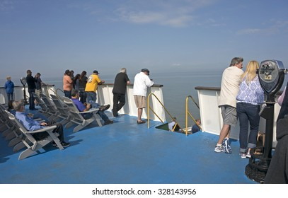Lewes Delaware October 7, 2015: Passengers stand on the upper deck of the Cape Henlopen ferry looking out into the Delaware Bay during a crossing from Lewes Delaware to Cape May New Jersey.