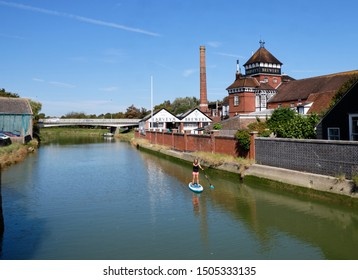 Lewes, East Sussex, UK. 13th September, 2019.  Beautiful sunny afternoon in Lewes with a paddle border riding Ouse river by Harvey's Brewery building
