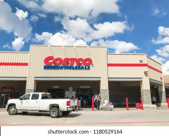 Lewisville, TX, USA-SEPT 15, 2018:White truck driving by entrance of Costco Wholesale with customer carry purchase cart leaving. The largest membership-only warehouse club in USA, cloud blue sky