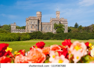 Lews Castle in Stornoway, United Kingdom with blurred roses in foreground. Castle with green grounds on blue sky. Historic architecture and design. Landmark and attraction. Summer vacation on isle.