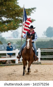 LEXINGTON, KENTUCKY - OCTOBER 29: Man rides holding American flag as a spectator salutes the flag on October 29, 2013 in Lexington, Kentucky
