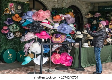 LEXINGTON, KY/USA - APRIL 19, 2018: A woman dressed for chilly weather takes a photo of fancy hats at a millinery shop before the first thoroughbred race of the afternoon at Keeneland Race Course.