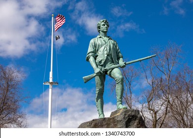 Lexington, MA / USA - March 16 2019: Minuteman statue at Lexington Green - centered with flag