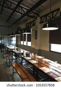 Leyte, Philippines; March 13, 2018: The dining area for customers of the Seafood and Ribs Warehouse restaurant in the town of Palo has long tables and overhead lamps.