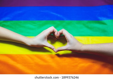 Lgbt community colorful flag. Two women's hands on rainbow background. Lesbian and gay problems. Legalization of marriage for couples with homosexual orientation.