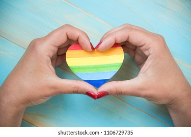 lgbt  concept, hands holds a heart painted like a LGBT flag on blue background. LGBT symbolic in heart shapes