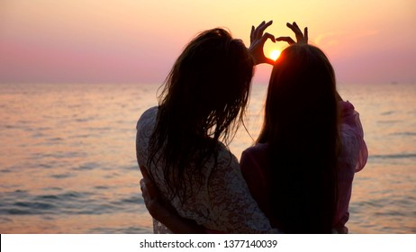 LGBT concept. A happy lesbian couple is resting on a beautiful tropical beach at sunset. girls stand embracing and make a heart with their hands, against the setting sun