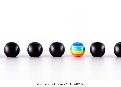 LGBT concept. Many black balls and one painted in the colors of the rainbow.