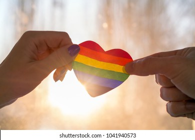 LGBT day concept,  hand holds a heart painted like a LGBT flag, silhouetted against sun