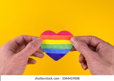 LGBT day concept,  heart of the rainbow LGBT flag in the hands yellow background