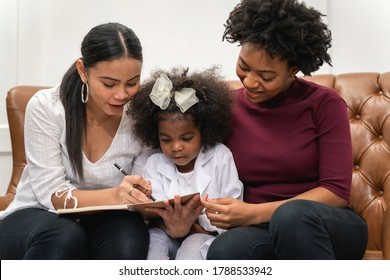 LGBT diversity Lesbian Couple Moments Happiness with her African girl laughing and drawing picture, Family concept
