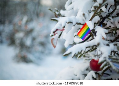 LGBT flag. Christmas background outdoor. Christmas tree covered with snow and decorations and flag. Christmas holiday greeting card.