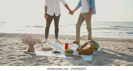 Lgbt gay couple having romantic picnic at the beach, holding hand each other, standing behind blanket with wine, glasses and food.