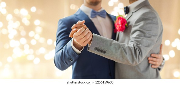 lgbt, homosexuality and same-sex marriage concept - close up of happy male gay couple holding hands and dancing on wedding over festive lights background