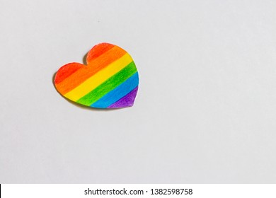 lgbt and human rights minimal concept, a paper cutout heart colored like a LGBT flag isolated on white background