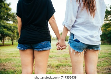 LGBT lesbian women couple moments happiness. Lesbian women couple together outdoors concept. Lesbian couple holding hands together relation fall in love. Two asian women having fun together at park.