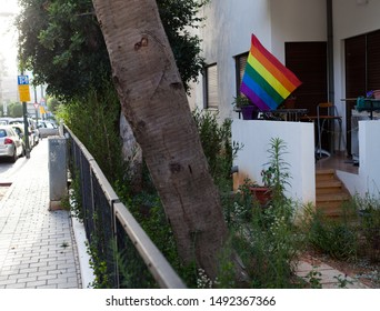 The LGBT pride flag at the porch in the ground floor of an apartment building.